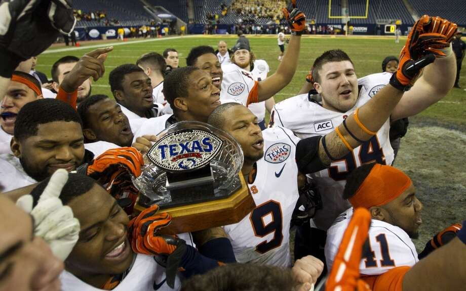 Syracuse players hold the Texas Bowl trophy as they celebrate their 21-17 win over Minnesota at Reliant Stadium, Friday, Dec. 27, 2013, in Houston. ( Brett Coomer / Houston Chronicle ) Photo: Brett Coomer, Houston Chronicle