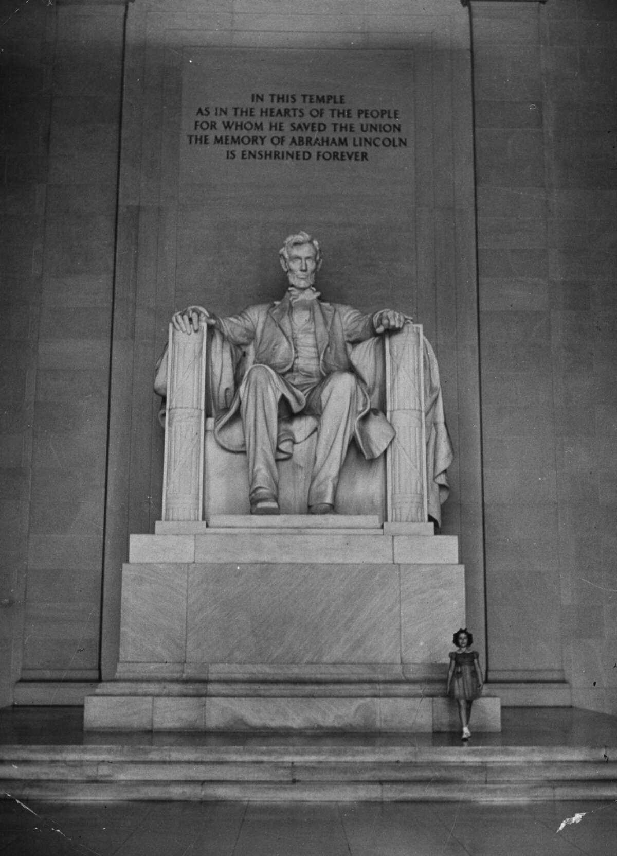 Circa 1930s: Actress Shirley Temple standing beside the Lincoln Memorial.