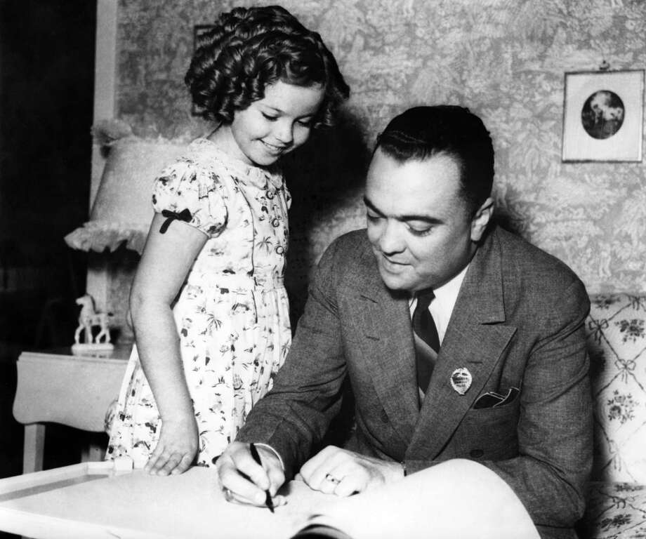 1937: John Edgar Hoover, Director of the Federal Bureau of Investigation (FBI) of the United States, signs young actress Shirley Temple's autograph books, after he was made a member of the Shirley Temple Police Force. Photo: -, AFP/Getty Images / 2014 AFP