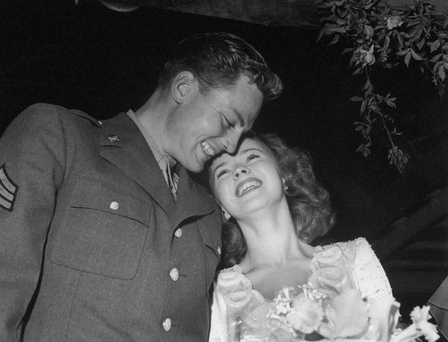 1945: Actress Shirley Temple, 17, with her husband, Air Force Sgt. John Agar, 24, at wedding reception at her home. Photo: Frank Scherschel, Time & Life Pictures/Getty Image / Time Life Pictures