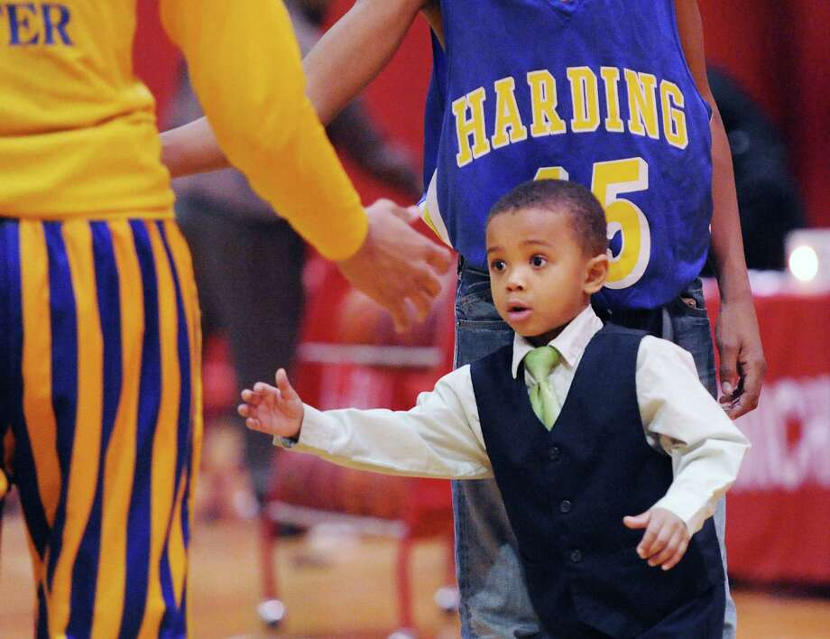 Cameron Clemons, 3, the son of Harding basketball coach, Charles Clemons, slaps hands with a Harding player before the start of th high school basketball game between Warren Harding High School and Greenwich High School at Greenwich, Friday night, Feb. 7, 2014. Photo: Bob Luckey / Greenwich Time