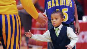 Cameron Clemons, 3, the son of Harding basketball coach, Charles Clemons, slaps hands with a Harding player before the start of th high school basketball game between Warren Harding High School and Greenwich High School at Greenwich, Friday night, Feb. 7, 2014.