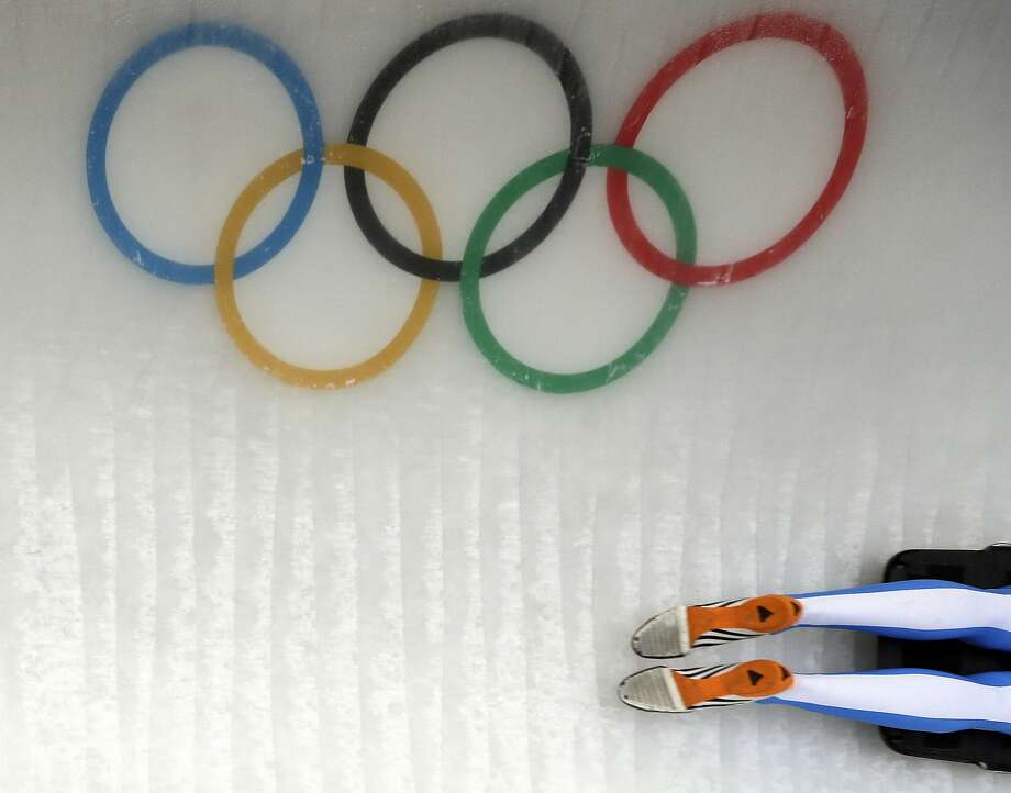 The feet of Maurizio Oioli of Italy pass the Olympic Rings as he speeds down the track during the men's skeleton training at the 2014 Winter Olympics, Tuesday, Feb. 11, 2014, in Krasnaya Polyana, Russia. Photo: Natacha Pisarenko, Associated Press