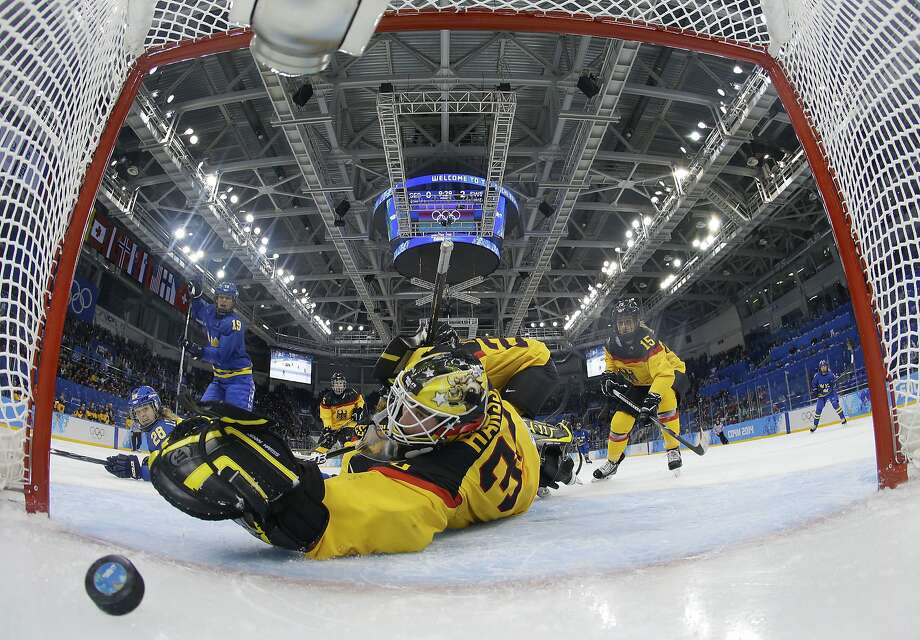 Goalkeeper Jennifer Harss of Germany reaches for the puck as Johanna Olofsson's of Sweden shot get by her for a goal during the third period of women's ice game at Shayba Arean during the 2014 Winter Olympics, Tuesday, Feb. 11, 2014, in Sochi, Russia.  Photo: Mark Blinch, Associated Press