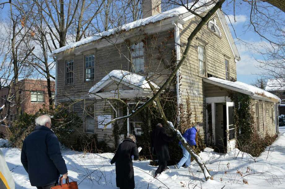 Members of the Historic District Commission climb through snow drifts to tour two blighted Post Road West houses Monday that they would like to convince the owner to save from planned demolition. Photo: Jarret Liotta / Westport News contributed