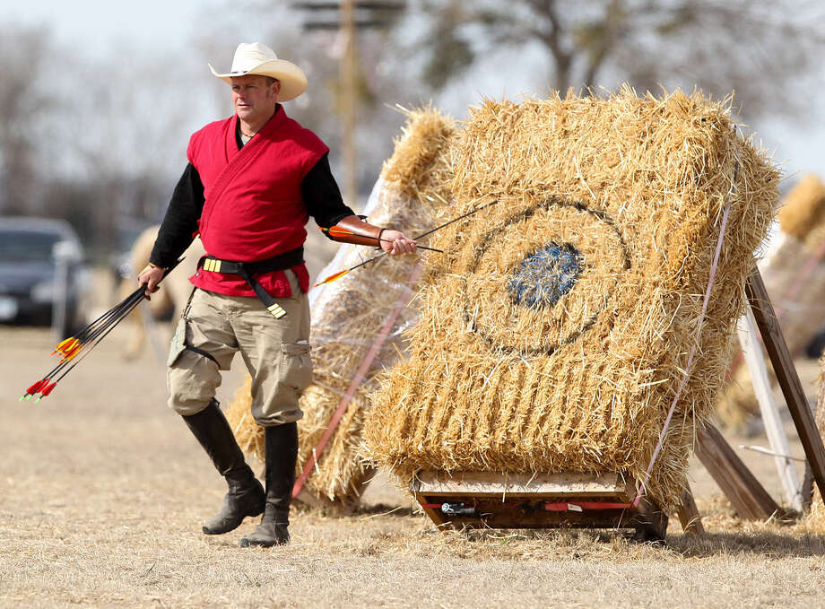 Trey Schlichting pulls arrows from a hay bale used as a target during a recent training session in New Braunfels. / Prime Time Newspapers 2014