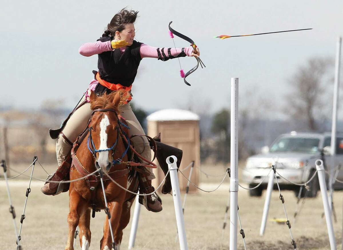 Kayla Nash, 15, sends an arrow flying at the target on the 90-meter Hungarian course while astride her horse during a mounted archery training session for the Bi-Continental Championship.