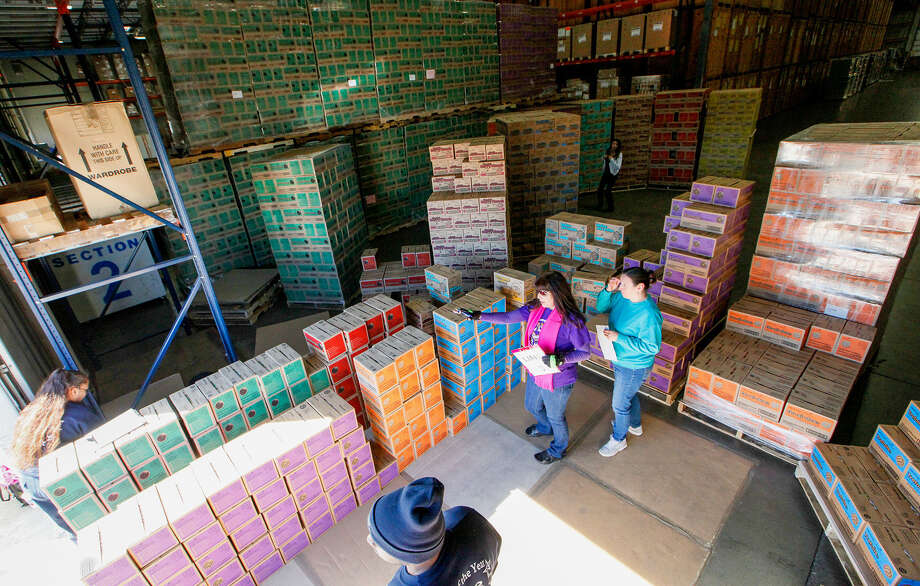 Kathryn Foley, center, confirms Girl Scout Troop 454's order with Cynthia Michaud, right, at the warehouse where cookies are stored just prior to distribution. Photo: Photos By Marvin Pfeiffer / Helotes Weekly / Prime Time Newspapers 2014