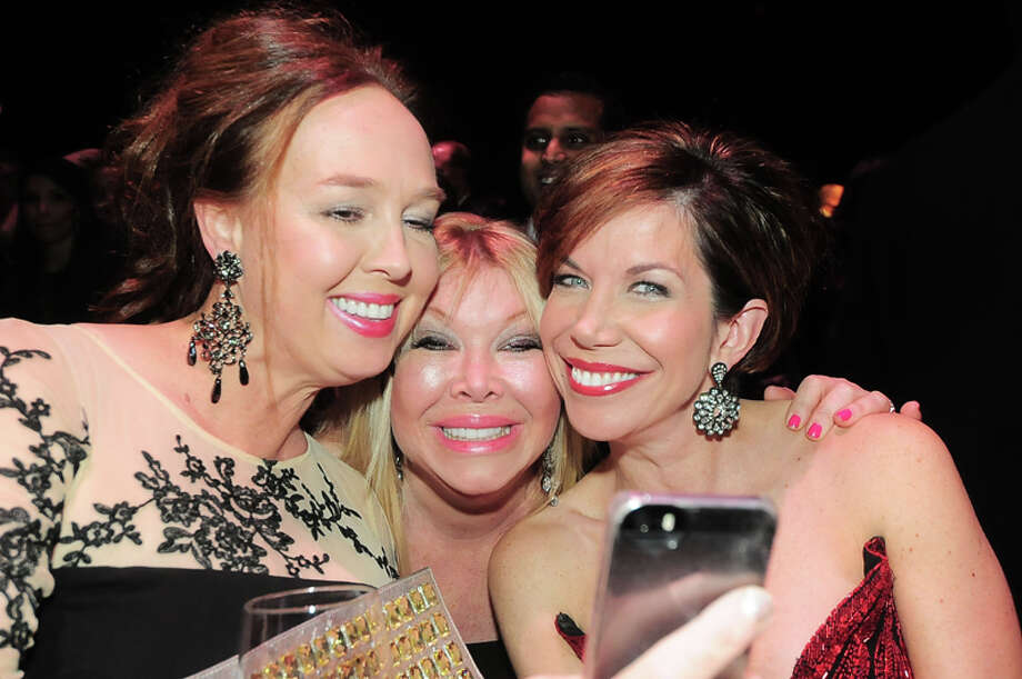 Julie Brown shows a photo to Lara Bell and Roseann Rogers at the American Heart Association's 31st Annual Houston Heart Ball at The Hobby Center Saturday 02/08/14. Photo by Tony Bullard. Photo: © Tony Bullard 2014, For The Chronicle / © 2014 Tony Bullard