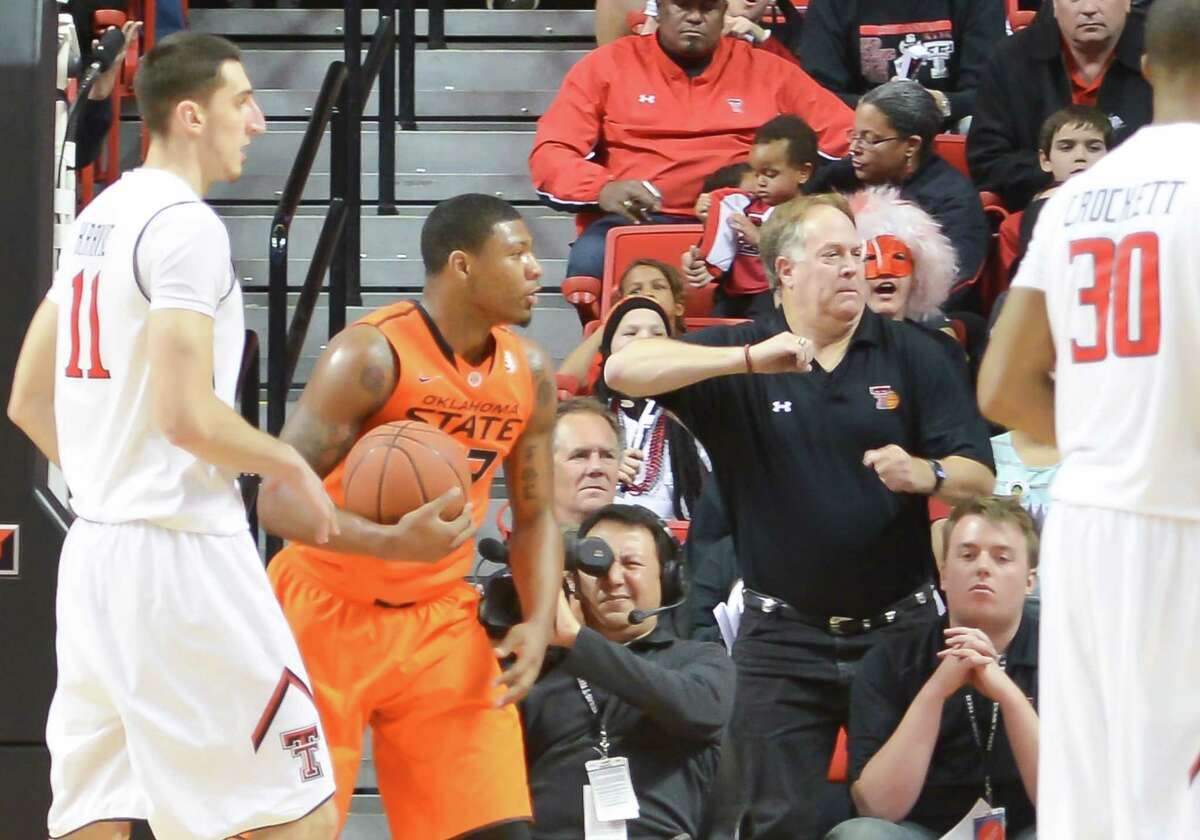 On Monday, Oklahoma State suspended basketball star Marcus Smart (in orange) for three games after he shoved Texas Tech fan Jeff Orr at the end of a game Saturday night in Lubbock, Texas. Smart initially claimed Orr had directed a racial slur at him, while Orr (in black shirt) maintained he simply called Smart a
