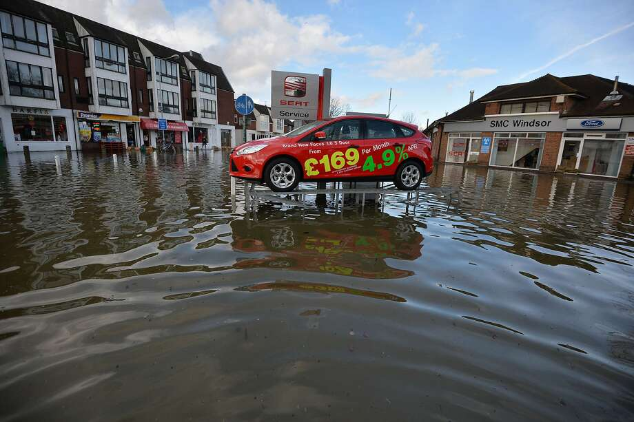 Above it all:At least one car is staying high and dry after the River Thames burst its banks in Dachet, England - a display auto sitting on an elevated platform at a car dealership. Photo: Ben Stansall, AFP/Getty Images