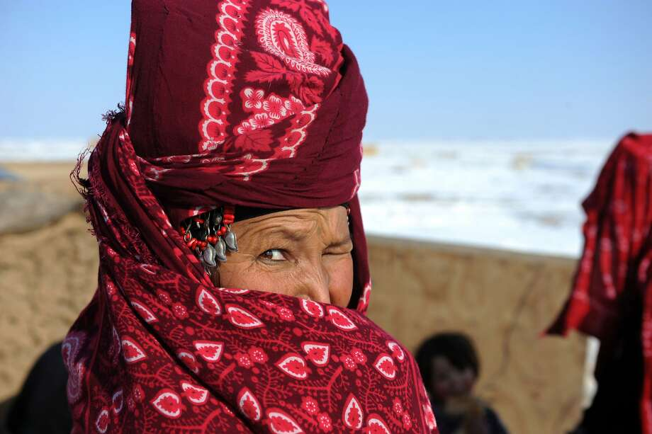 One-eyed stare:A displaced woman covers her face as she stands at the Sakhi camp in Mazar-i-Sharif, 