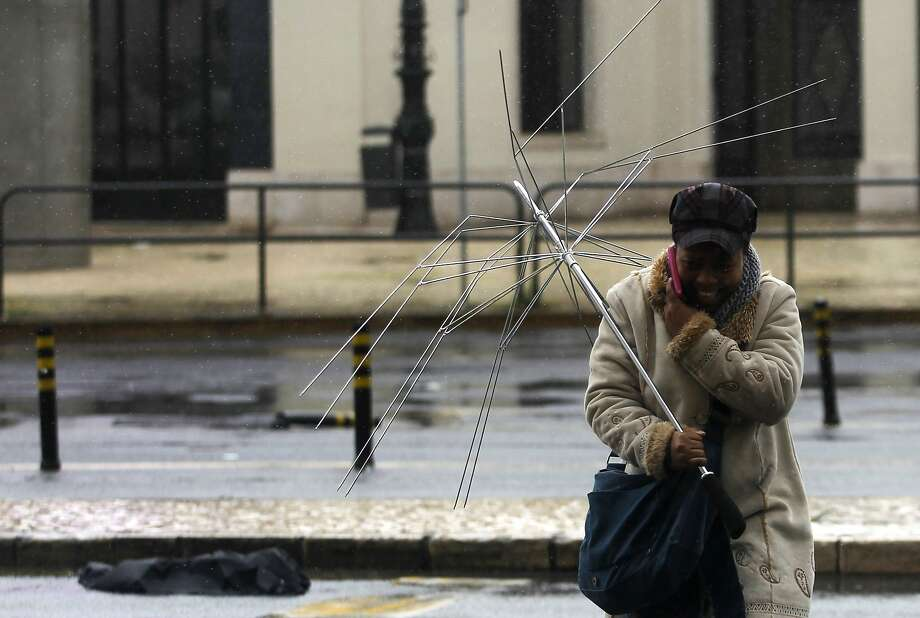 Signs you need a new umbrella:1) When it begins to resemble a TV antenna. (Lisbon.) Photo: Francisco Seco, Associated Press