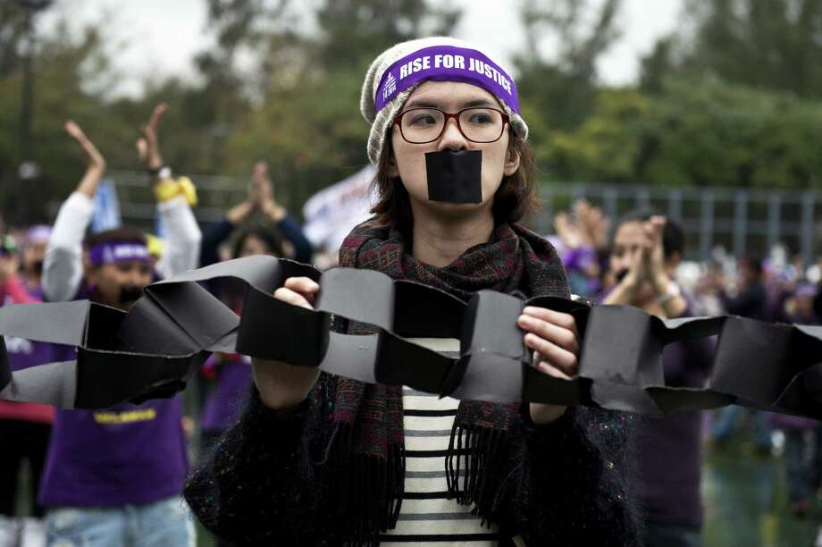 "A demonstrator holds a symbolic cardboard chain at a ""One Billion Rising for Justice"" rally in Hong Kong on February 9, 2014, where hundreds of protesters danced and rallied for the rights of domestic helpers and migrants, in particular calling for justice for an Indonesian maid who fled the city in January after being allegedly tortured by her Hong Kong employer. The alleged maltreatment of Erwiana Sulistyaningsih, who left a hospital in Java on February 5 after a month of treatment following what she described as a horrific ordeal for eight months in Hong Kong, has renewed concerns about the treatment of domestic helpers in the southern Chinese city following similar cases and criticism from rights groups.  AFP PHOTO / ALEX OGLEAlex Ogle/AFP/Getty Images Photo: ALEX OGLE / AFP"