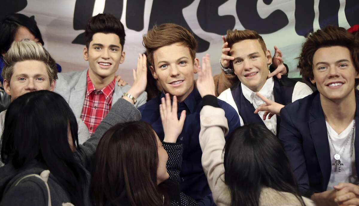 Please don't melt the boy band, girls:Japanese fans grab the wax figures of One Direction members during an unveiling ceremony at Madame Tussauds in Tokyo.