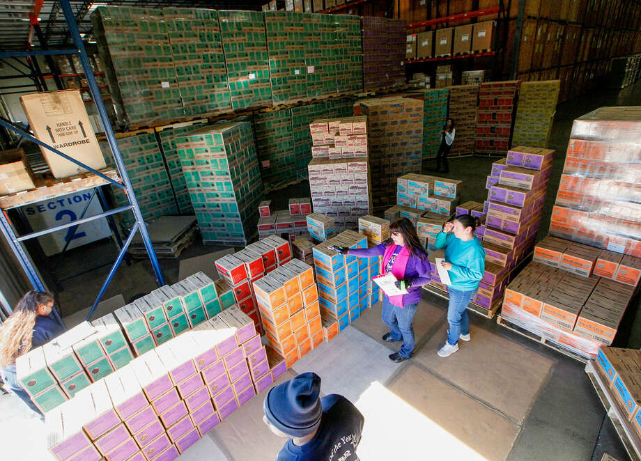 Kathryn Foley, center, confirms Girl Scout Troop 454's order with Cynthia Michaud, right, at the warehouse in San Antonio where the cookies are stored just prior to distribution. Photo: Marvin Pfeiffer / Stone Oak Weekly / Prime Time Newspapers 2014