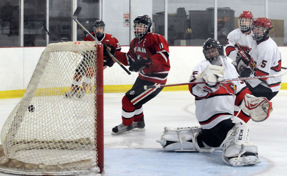 New Canaan's John O'Rourke puts the puck in the net as Greenwich hosts New Canaan High School in a boys hockey game at Dorothy Hamill Rink in Greenwich, Conn., Feb. 8, 2014. Photo: Keelin Daly / Stamford Advocate Freelance