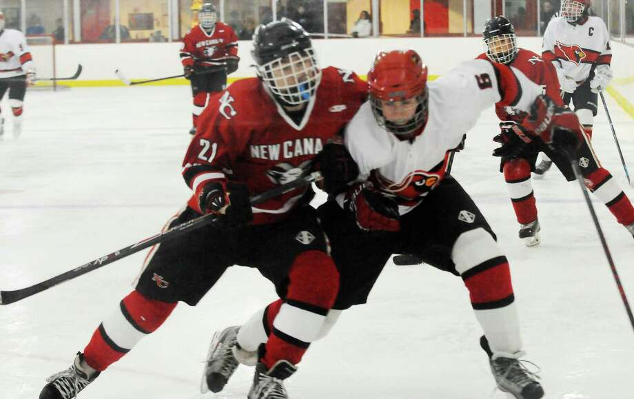 New Canaan's Parker Lewis and Greenwich's Eamon McHugh in action as Greenwich hosts New Canaan High School in a boys hockey game at Dorothy Hamill Rink in Greenwich, Conn., Feb. 8, 2014. Photo: Keelin Daly / Stamford Advocate Freelance