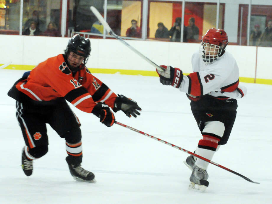 Ridgefield's James Kelly and Greenwich's Kevin Piotrzkowski in action as Greenwich hosts Ridgefield High School in a boys hockey game at Dorothy Hamill Rink in Greenwich, Conn., Jan. 30, 2014. Photo: Keelin Daly / Stamford Advocate Freelance