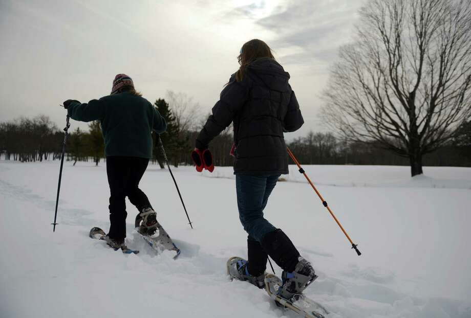 Fay Gerstenfeld, left, and Allison Archambault, of Ridgefield, trek through the snow during the Discovery Center of Ridgefield's snowshoeing expedition at the Ridgefield Golf Club in Ridgefield , Conn. Sunday, Feb. 9, 2014.  The Discovery Center has a weekly hiking group open to members and non-members that frequently goes snowshoeing in the wintertime. Photo: Tyler Sizemore / The News-Times