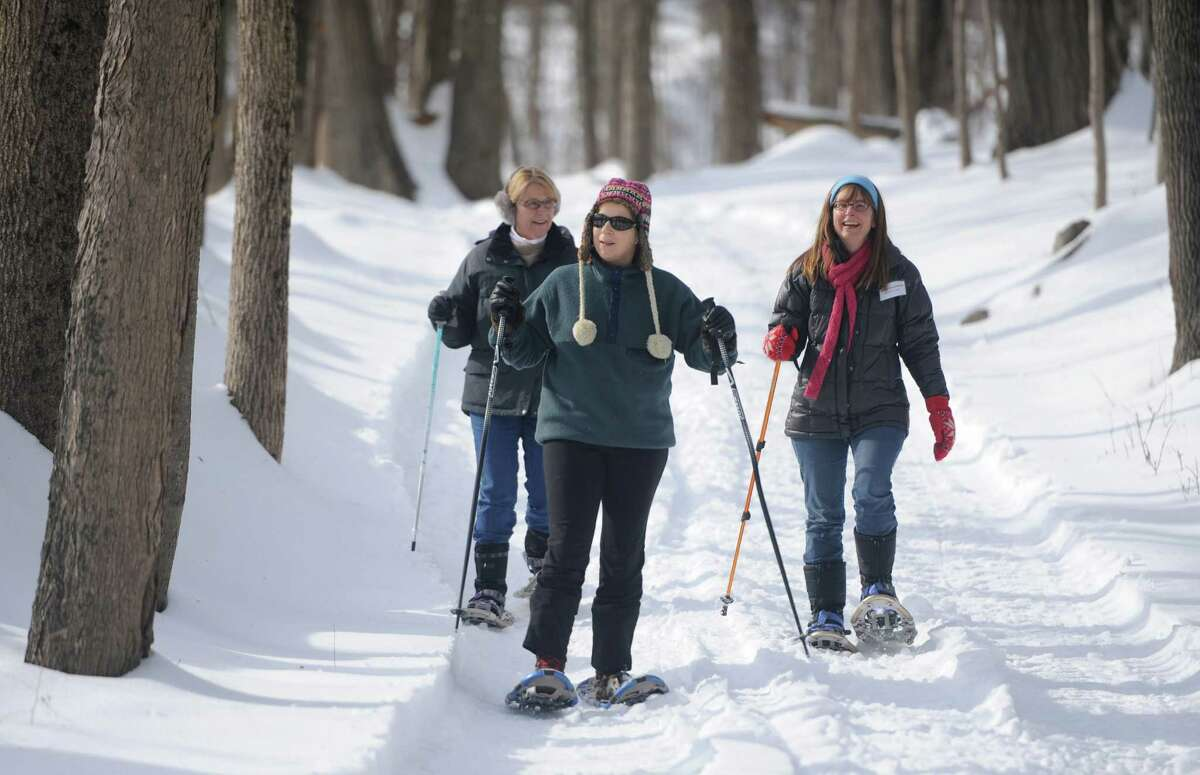 Debbie Sutcliffe, left, of Redding, Fay Gerstenfeld, center, of Ridgefield, and Allison Archambault, of Ridgefield, hike on a trail in the woods at the Discovery Center of Ridgefield's snowshoeing expedition at the Ridgefield Golf Club in Ridgefield.