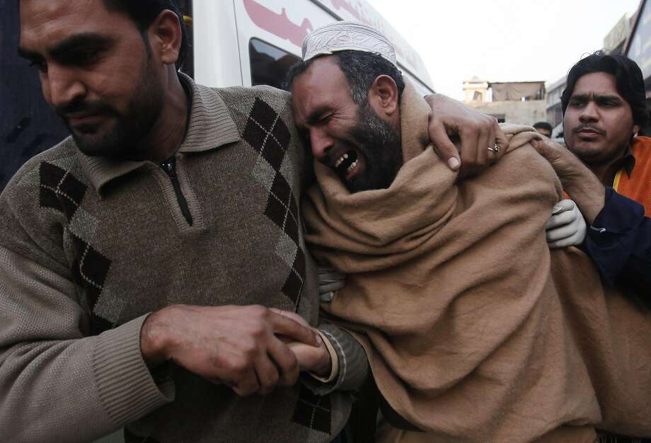 A man grieving over the death of his brother in a grenade attack on a Peshawar cinema is comforted. Photo: Fayaz Aziz, Reuters