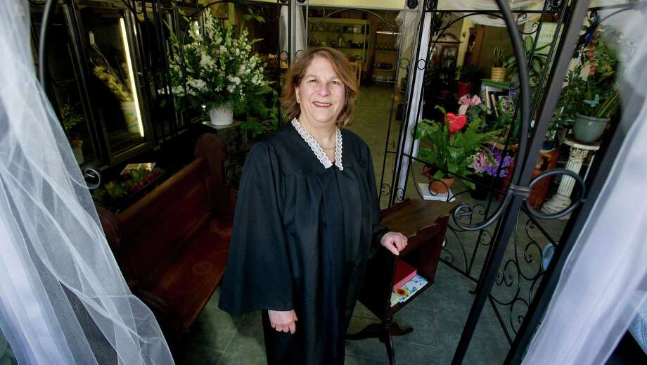 Margaret Cluceru poses for a photo in her Justice of the Peace robes on Tuesday, February 11, 2014, at Nobu Florist in Stamford, Conn., where she performs wedding ceremonies in-store. Photo: Lindsay Perry / Stamford Advocate