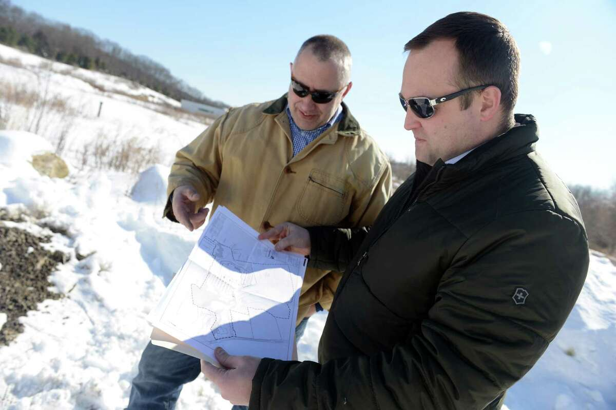 Developer John Kimball and Kevin Solli, whose engineering firm designed the project, look over plans for the future site of a 161,000-square-foot retail project near Swiss Army corporate headquarters in Monroe.