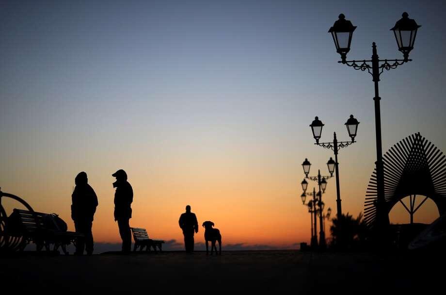 Police patrol along the boardwalk on the Black Sea accompanied by a stray dog outside the Olympic Park at the 2014 Winter Olympics, Monday, Feb. 3, 2014, in Sochi, Russia. (AP Photo/David Goldman) Photo: David Goldman, Associated Press