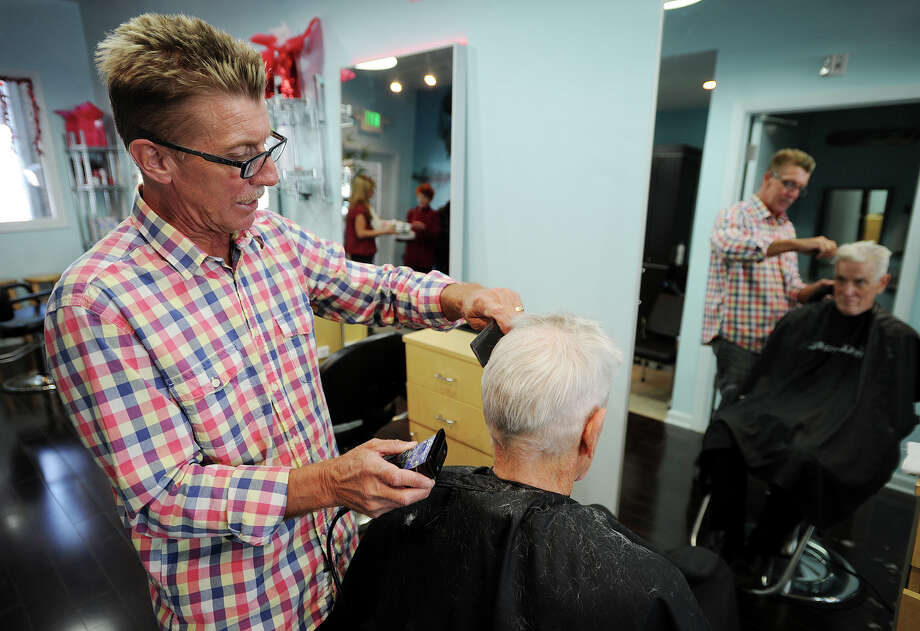 Mark Sullivan gives a haircut to customer Mike Siegman, of Milford, at Looks Hair Design at 122 South Broad Street in Milford, Conn. on Tuesday, February 11, 2014. Sullivan and his wife Diana have operated the business in Milford for 20 years. Photo: Brian A. Pounds / Connecticut Post