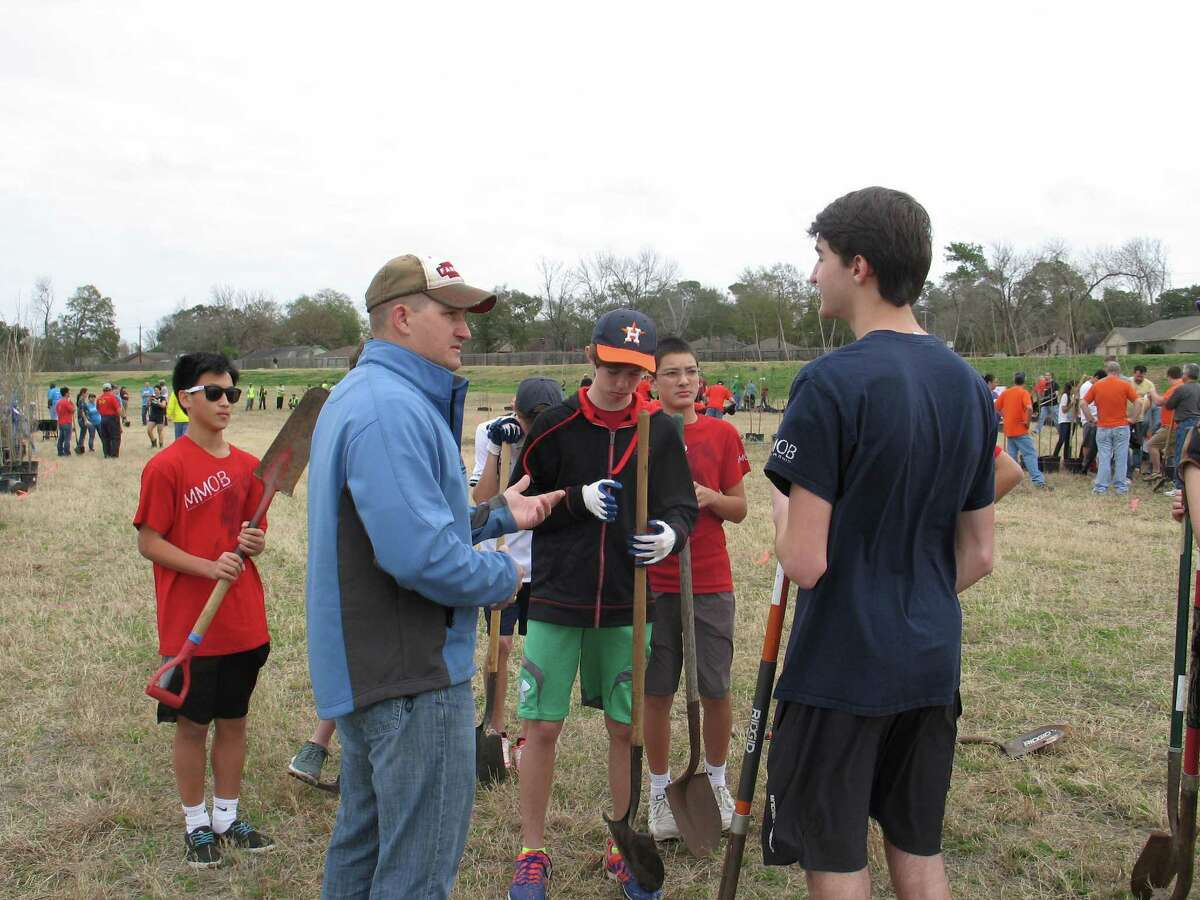 Harris County Flood Control District forester Shane Hrobar gives volunteers from a Memorial High School team some pre-competition planting tips.