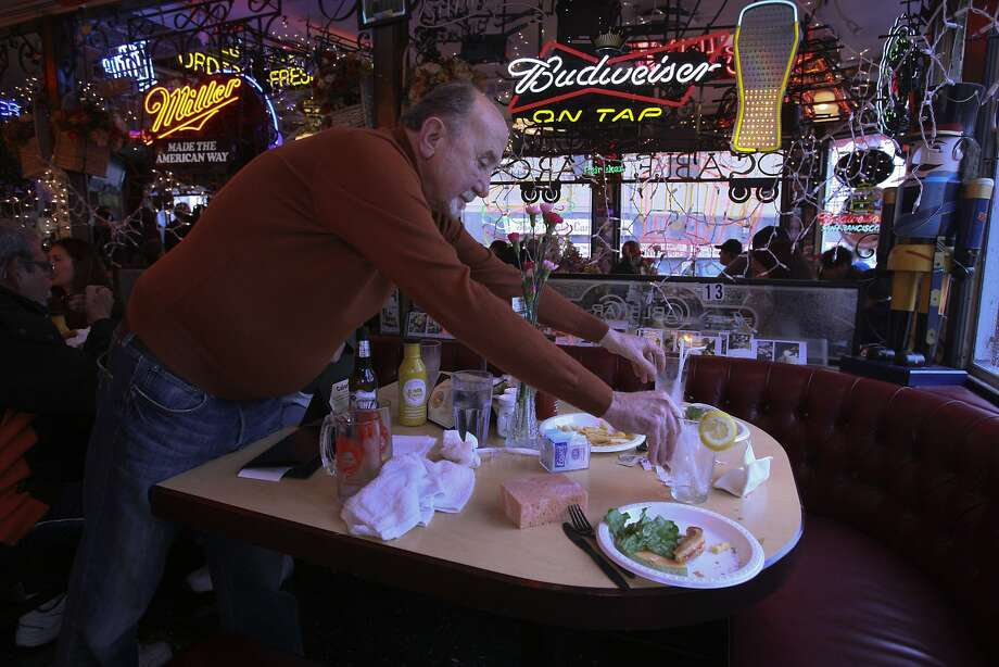 Joe Obegi cleans a table at Joe's Cable Car Restaurant, which began in 1965 as a tiny spot serving takeout and grew into a maze of tables in the 1980s. Photo: Andre Zandona, The Chronicle