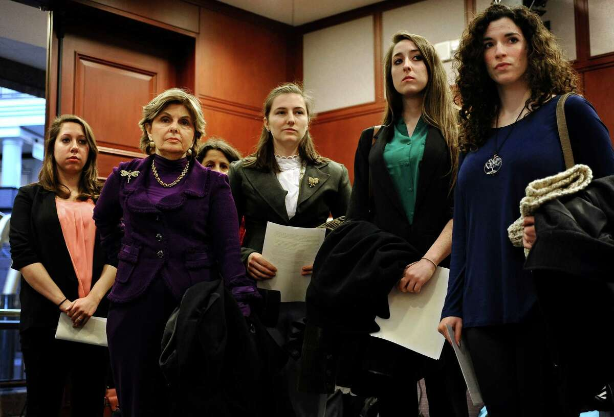 Attorney Gloria Allred, second right, stands with clients Erica Daniels, left, Kylie Angell, center, Carolyn Luby, second from right, and Rosemary Richi before they testify at a public hearing on sexual assaults and procedures at the Legislative Office Building Wednesday, Nov. 13, 2013, in Hartford, Conn. The women, who say they were victims of sexual assaults while students at UConn, have filed a federal discrimination lawsuit against the school.