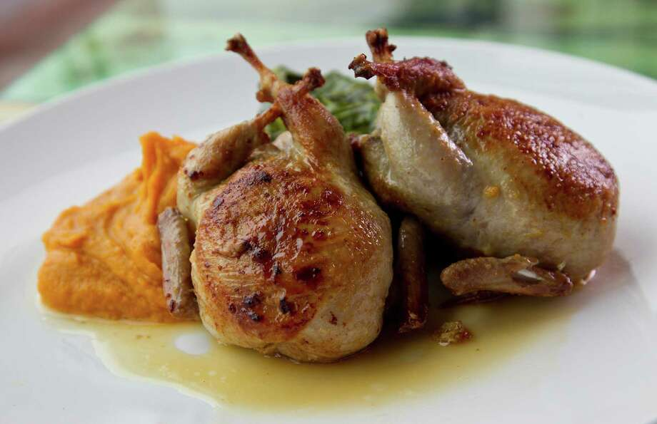 The Texas Semi-Boneless Quail (seared andouille cornbread stuffing, west potatoes and satsuma gastrique) comes with chef Antoine Ware's fantastic greens. Photo: Karen Warren, Staff / © 2013 Houston Chronicle