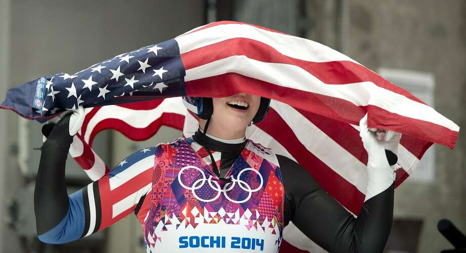 Erin Hamlin of the United States celebrates with the American flag after finishing her final run to win the bronze medal in the women's singles luge competition at the 2014 Winter Olympics, Tuesday, Feb. 11, 2014, in Krasnaya Polyana, Russia. (AP Photo/The Canadian Press, Jonathan Hayward) Photo: Jonathan Hayward, Associated Press
