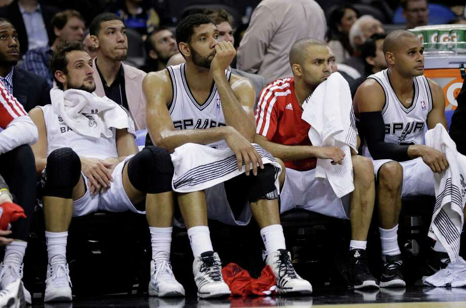 San Antonio Spurs players, from left, Marco Belinelli, Tim Duncan, Tony Parker, and Patty Mills  sit on the bench during the second half of an NBA basketball game against the Chicago Bulls, Wednesday, Jan. 29, 2014, in San Antonio.  Chicago won 96-86. (AP Photo/Eric Gay) Photo: Eric Gay, Associated Press / AP