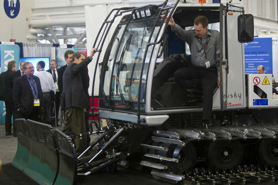 Andrew Bricker steps down from an all terrain vehicle to move snow during the Arctic Technology Conference at the George R. Brown Convention Center in Houston, Tuesday, Feb. 11, 2014. Photo: Marie D. De Jesús, Houston Chronicle