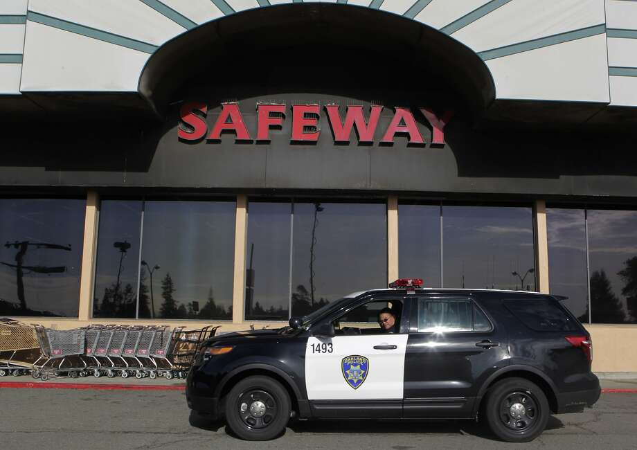 Police sit outside an Oakland Safeway where a reported carjacking and kidnapping led to an Amber Alert. Photo: Paul Chinn, The Chronicle