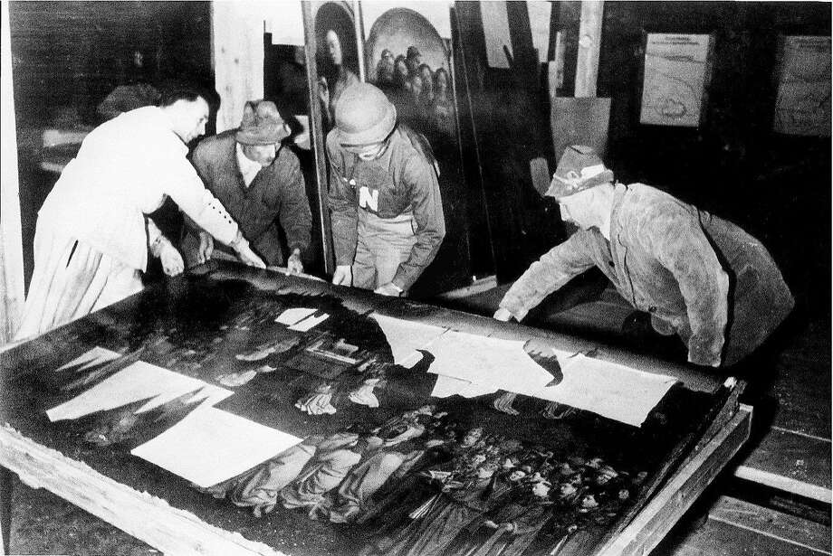 "This photo provided by The Monuments Men Foundation for the Preservation of Art of Dallas, shows Monuments Man George Stout, third from left with an ""N"" on his shirt, moving the central panel of the Ghent Altarpiece in Altaussee, Austria in July of 1945. From a fairy tale-inspiring castle in the Bavarian Alps to a serene sculpture of Mary and Jesus by Michelangelo tucked away in a church in Belgium, sites and works of art across Europe can give travelers a glimpse at the heroic work done by those who worked to save cultural treasures during World War II.  (AP Photo/National Archives and Records Administration) Photo: Associated Press"