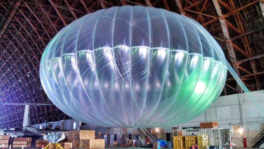 Google tests a fully inflated balloon in a hangar in March 2013. The balloons sail in the stratosphere and beam the Internet to Earth. (AP Photo/Google, Andrea Dunlap) Photo: Andrea Dunlap, Associated Press