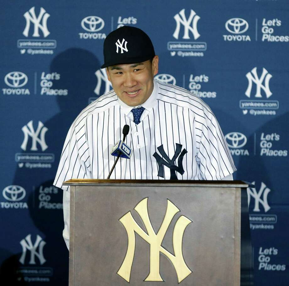 New York Yankees pitcher Masahiro Tanaka, of Japan, speaks as Yankees owner Hal Steinbrenner, left, watches him during a news conference at Yankee Stadium Tuesday, Feb. 11, 2014, in New York.  (AP Photo/Frank Franklin II) ORG XMIT: NYY104 Photo: Frank Franklin II / AP