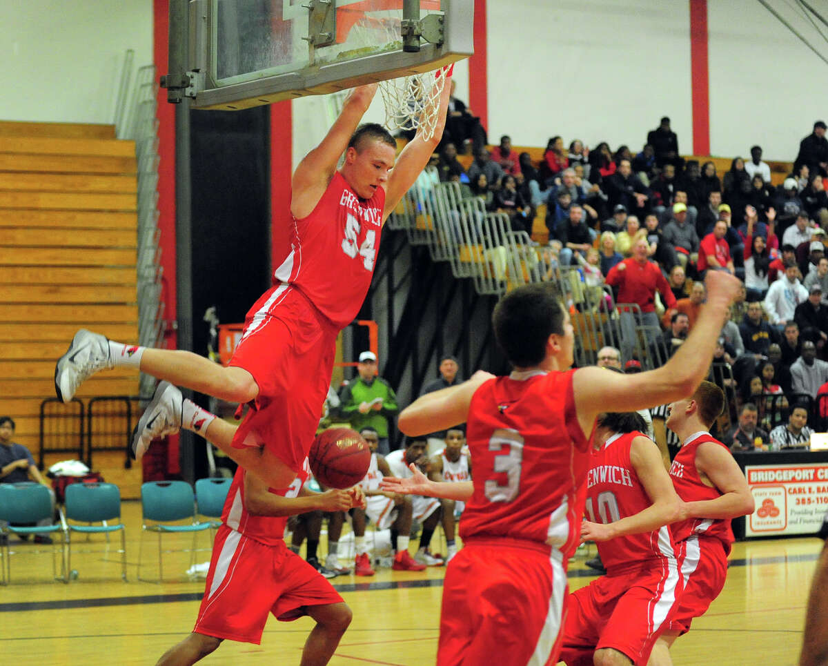 Greenwich's Alex Wolf hangs onto the rim after a slam dunk, during boys basketball action against Central in Bridgeport, Conn. on Tuesday February 11, 2014.