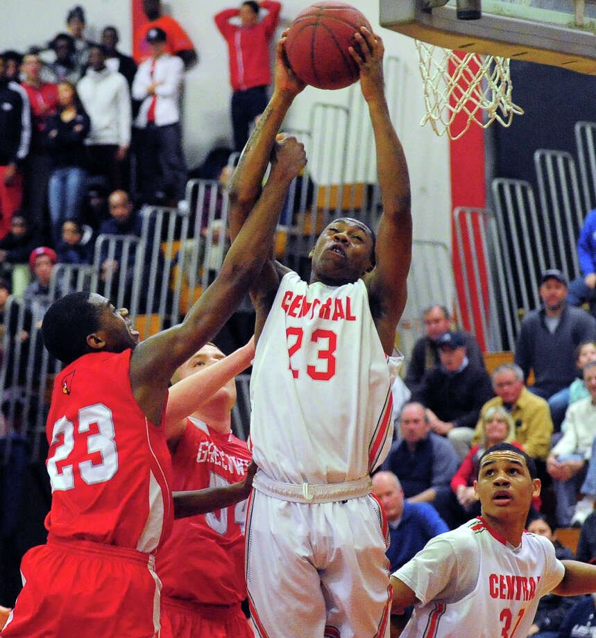 Central's Antoin Pettway grabs a Greenwich rebound, during boys basketball action against Greenwich in Bridgeport, Conn. on Tuesday February 11, 2014. At left is Greenwich's Leonel Hyatt. Photo: Christian Abraham / Connecticut Post