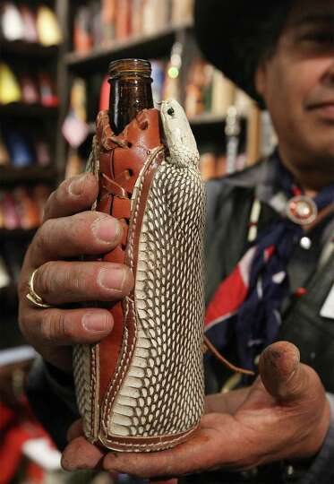 Vendor Joe Moreno, owner of Texas Leather Coozy, holds a drink holder made of leather and a spitting