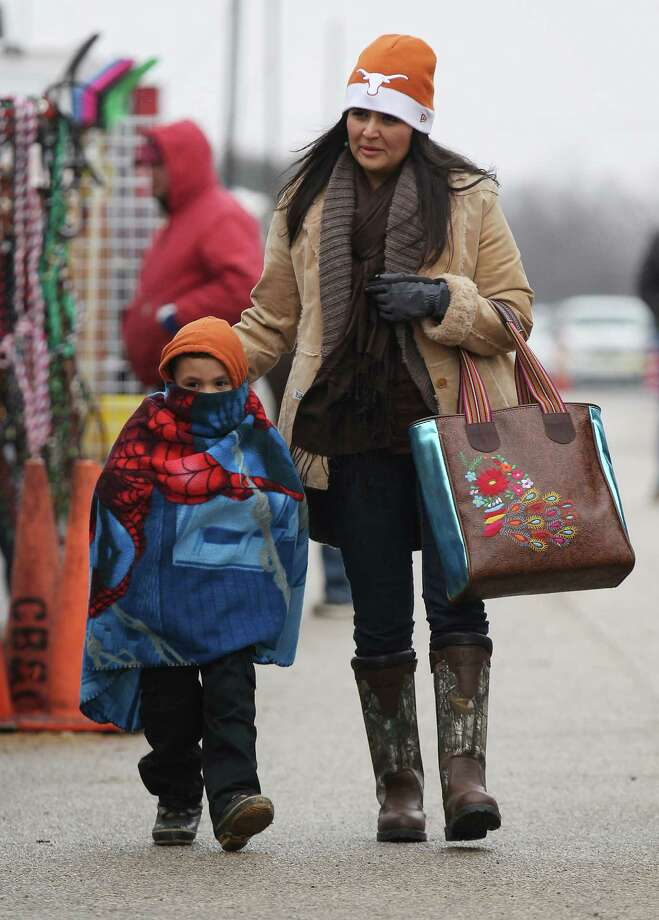 Claudia De La Cruz from McAllen, Texas covers her four-year-old son, Adan, with a blanket to shield him from the cold as they peruse the grounds of the 2014 San Antonio Stock Show and Rodeo on Tuesday, Feb. 11, 2014. Another blast of near-freezing temperatures kept some spectators and participants away from the stock show. Tuesday, however, marked the first full day for junior livestock participants to bring in their animals for the upcoming judging and competitions. Photo: Kin Man Hui, San Antonio Express-News / ©2013 San Antonio Express-News