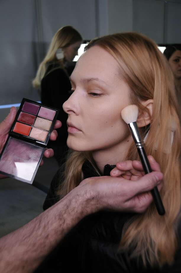 Senior MAC cosmetics makeup artist Victor Cembellin applies makeup to a model's face for the Ostwald Helgason show Feb. 8 at Milk Studios. Photo: Luca Cannonieri