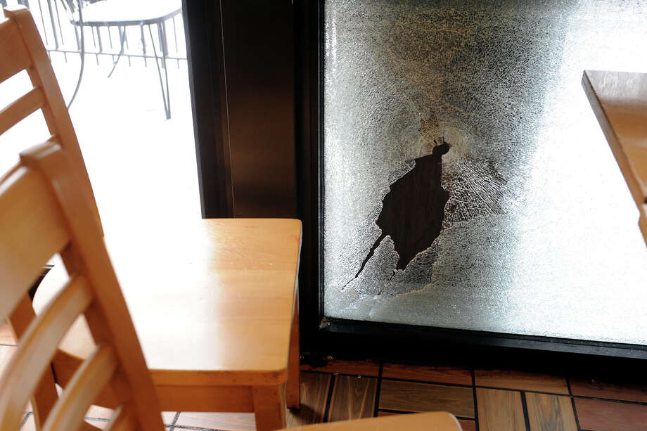 A bullet hole and shattered window where a Bridgeport Police Officer accidently shot himself during breakfast at the Bagel King on upper Main St., in Bridgeport, Conn., Dec. 17, 2013. Photo: Ned Gerard / Connecticut Post