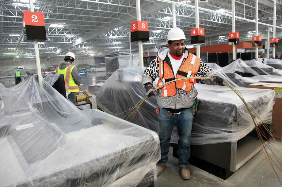 Anthony Davis installs wiring Tuesday at the new H-E-B grocery store in Pearland. The grocer is expected to open new locations in Grant/Spring-Cypress, League City, The Woodlands and Tanglewood this year. Photo: Mayra Beltran, Staff / © 2014 Houston Chronicle