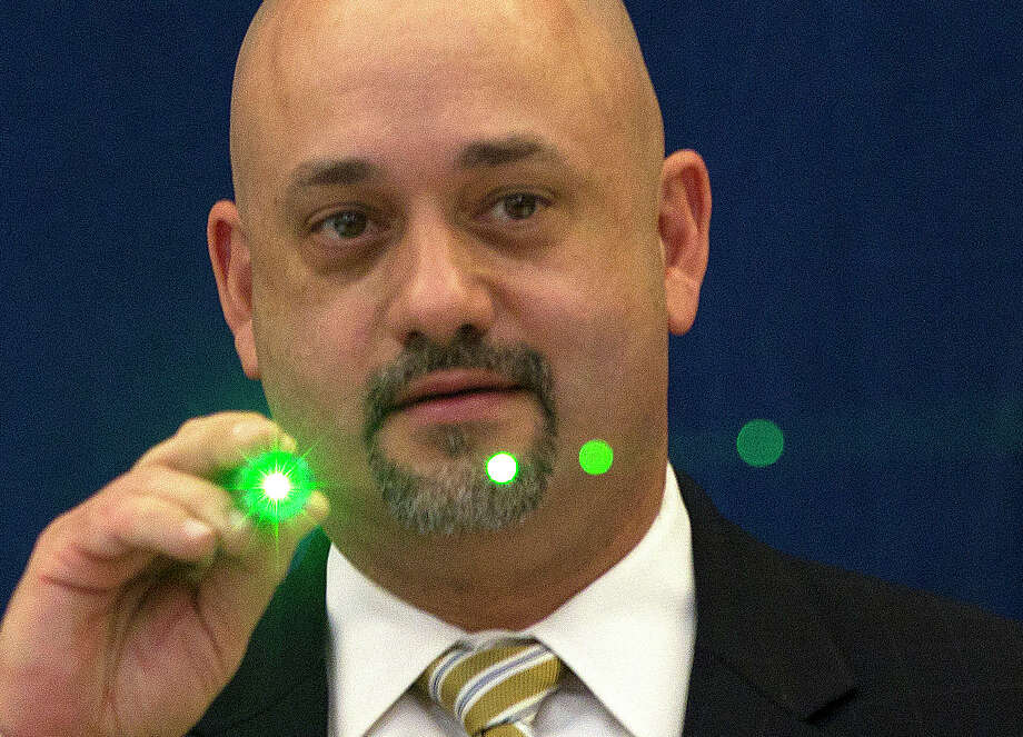 FBI Special Agent Stephen Morris demonstrates a laser pointer during a 2014 news conference on the dangers of aircraft laser strikes. Houston is one of the leading cities for such incidents. Photo: Johnny Hanson, Staff / © 2014  Houston Chronicle