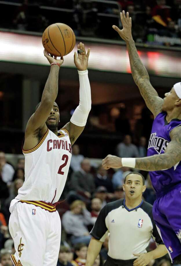 Cleveland Cavaliers' Kyrie Irving (2) makes a 3-point shot against Sacramento Kings' Isaiah Thomas during the fourth quarter of an NBA basketball game Tuesday, Feb. 11, 2014, in Cleveland. The Cavaliers won 109-99. (AP Photo/Mark Duncan) ORG XMIT: CDA109 Photo: Mark Duncan / AP